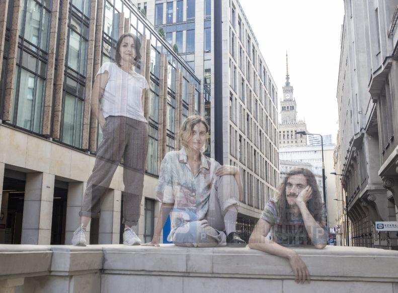 Jak zupełnie zniknąć / Trzy osoby ledwo widoczne na tle Pałacu Kultury i Nauki w Warszawie